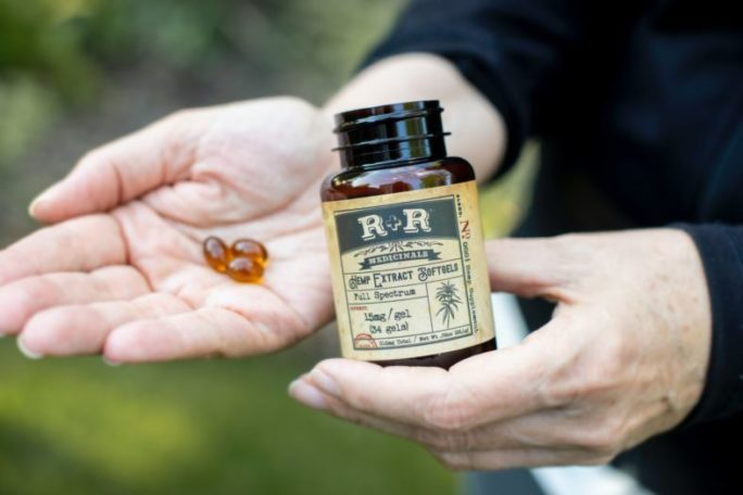 person holding R+R bottle and 3 gel capsules